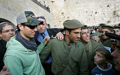 Spanish-born singer Enrique Iglesias poses for a picture with Israeli soldiers at the Western Wall, Judaism's holiest site, during a visit to Jerusalem's Old City, December 21, 2006. (AP Photo/Oded Balilty)