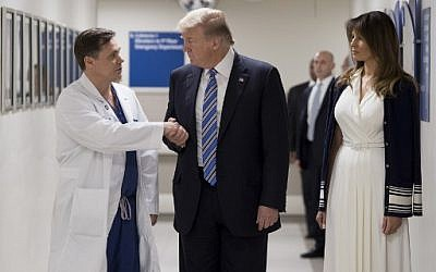 US President Donald Trump shakes hands with doctor Igor Nichiphorenko (L) beside First Lady Melania Trump while visiting first responders at Broward Health North hospital Pompano Beach, Florida, on February 16, 2018. (AFP PHOTO / JIM WATSON)