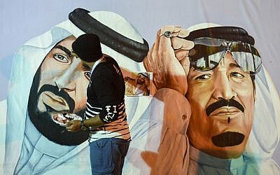 Saudi artists paint a mural portrait of King Salman bin Abdulaziz, right, and his son Crown Prince Mohammed bin Salman, during the 32nd Janadriyah Culture and Heritage Festival, held on the outskirts of the capital Riyadh on February 17, 2018. (AFP/Fayez Nureldine)