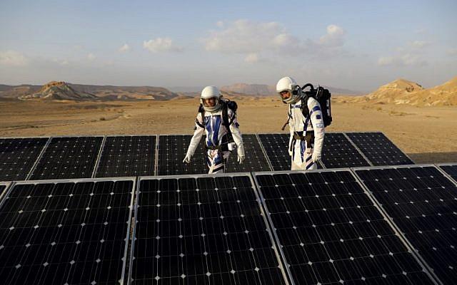 Israeli analog astronauts walk pat solar panels as they start their mission on the D-MARS Project on February 18, 2018. (AFP/ MENAHEM KAHANA)