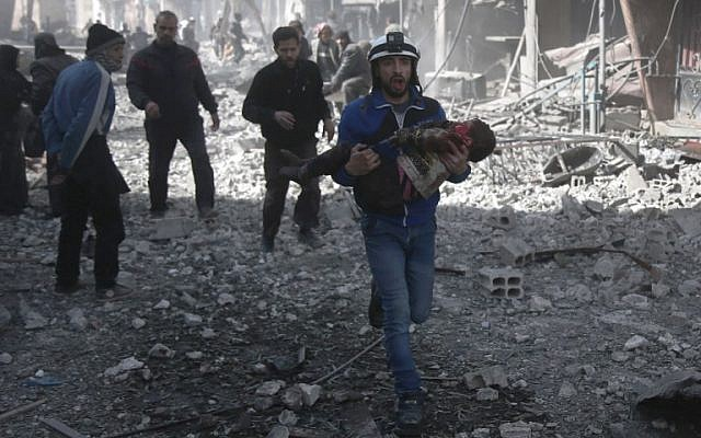 A Syrian civil defense member carries an injured child rescued from between the rubble of buildings following government bombing in the rebel-held town of Hamouria, in the besieged Eastern Ghouta region on the outskirts of the capital Damascus, on February 19, 2018. (AFP PHOTO / ABDULMONAM EASSA)