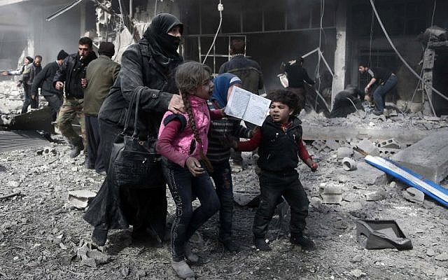 A Syrian woman and children run for cover amid the rubble of buildings following government bombing in the rebel-held town of Hammuriyeh, in the besieged Eastern Ghouta region on the outskirts of the capital Damascus, on February 19, 2018.(AFP Photo/Abdulmonan Eassa)