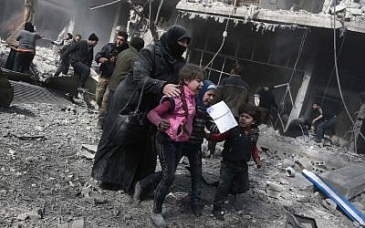 A Syrian woman and children run for cover amid the rubble of buildings following government bombing in the rebel-held town of Hamouria, in the besieged Eastern Ghouta region on the outskirts of the capital Damascus, on February 19, 2018. (AFP/Abdulmonam Eassa)