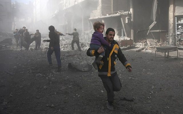 A Syrian man carries a child injured in government bombing in the rebel-held town of Hamouria, in the besieged Eastern Ghouta region on the outskirts of the capital Damascus, on February 19, 2018. (AFP PHOTO / ABDULMONAM EASSA)