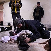 A man weeps over his child at a makeshift morgue in Douma who was killed in airstrikes on the Syrian village of Mesraba in the besieged Eastern Ghouta region on the outskirts of the capital Damascus, on February 19, 2018. (AFP PHOTO / Hamza Al-Ajweh)