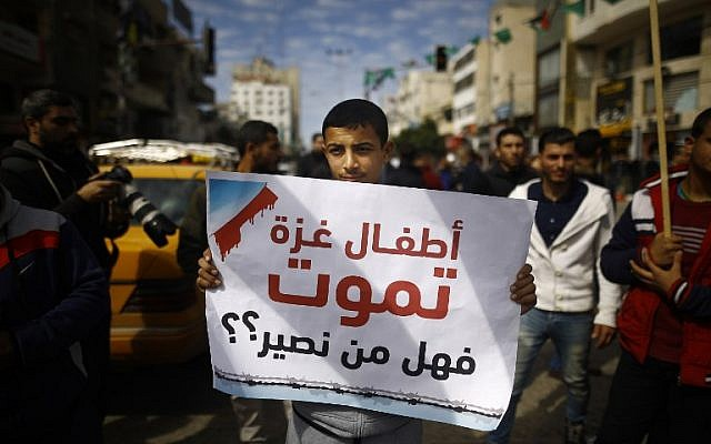 """A Palestinian holds a banner in Gaza City during a general strike to protest the humanitarian situation in Gaza on February 20, 2018. The writing in Arabic reads: """"Gaza's children are dying, can anyone help?"""" (AFP Photo/Mohammed Abed)"""