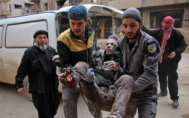 Civil Defense volunteers, known as the White Helmets, carry a wounded man into a makeshift hospital in the rebel-held town of Douma, following air strikes by regime forces on the besieged Eastern Ghouta region on the outskirts of the capital Damascus on February 20, 2018. (Hamza Al-Ajweh/AFP)