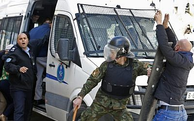 Palestinian police prevent demonstrators from approaching a police vehicle carrying members of the New York City council and civil society groups as they exit a building after visiting an NGO in the West Bank city of Ramallah on February 22, 2018. (Abbas Momani/AFP)
