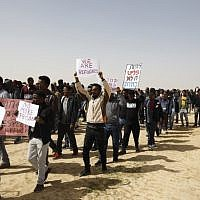 African migrants march from Holot detention center  to the Saharonim Prison, an Israeli detention facility for African asylum seekers, on February 22, 2018. (AFP  / MENAHEM KAHANA)