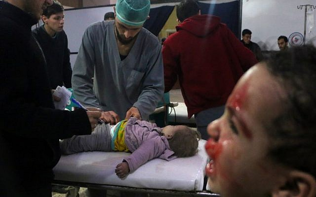 Syrian medics tend to a baby as a child cries next to them at a makeshift clinic following Syrian government bombardments in Douma, in the  besieged Eastern Ghouta region on the outskirts of the capital Damascus on February 22, 2018. (AFP/Hamza Al-Ajweh)