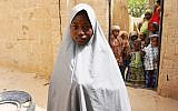 Hassana Mohammed, 13, who scaled a fence to escape an attack on her Government Girls Science and Technical College, stands outside her home in Dapchi, Nigeria, on February 22, 2018. (AFP PHOTO / AMINU ABUBAKAR)