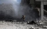 A civil defense volunteer, known as the White Helmets, checks the site of a regime air strike in the rebel-held town of Saqba, in the besieged Eastern Ghouta region on the outskirts of the capital Damascus, on February 23, 2018. (AFP PHOTO / ABDULMONAM EASSA)