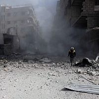 A Civil Defense volunteer, known as the White Helmets, checks the site of a regime air strike in the rebel-held town of Saqba, in the besieged Eastern Ghouta region on the outskirts of the capital Damascus, on February 23, 2018. (AFP Photo/Abdulmonam Essa)