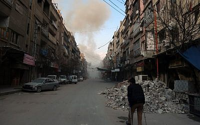 A Syrian man on crutches walks down a street as smoke billows in the rebel-held town of Douma, in the besieged Eastern Ghouta region on the outskirts of the capital Damascus, following airstrikes by regime forces on the area on February 23, 2018. (AFP/ HAMZA AL-AJWEH)