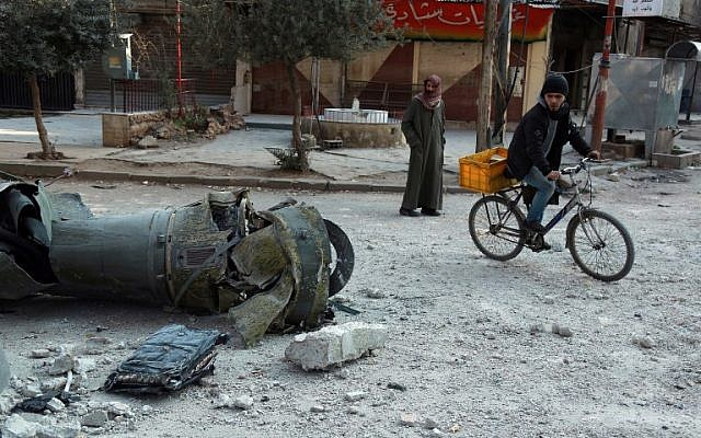 Syrian men walk past the remains of a rocket in the rebel-held town of Douma, in the besieged Eastern Ghouta region on the outskirts of the capital Damascus, following air strikes by regime forces on the area on February 23, 2018. (AFP PHOTO / HAMZA AL-AJWEH)
