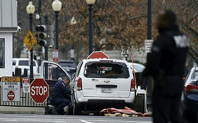 An agent inspects a passenger car sitting at a security barrier it  struck near the White House in Washington, DC, February 23, 2018. (AFP PHOTO / SAUL LOEB)