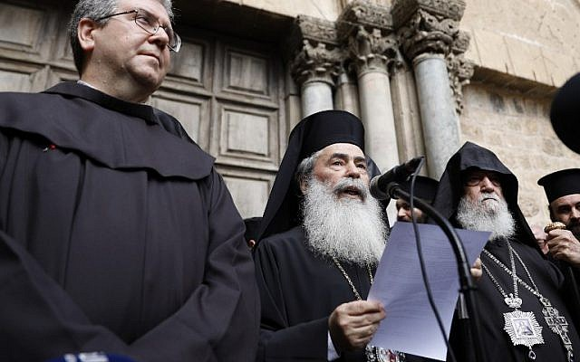 Greek Orthodox Patriarch of Jerusalem Theophilos III delivers a statement to the press as he stands next to the Custodian of the Holy Land Fr. Francesco Patton and Armenian Bishop Siwan (L) on February 25, 2018, outside of the closed doors of the Church of the Holy Sepulchre in Jerusalem's Old City. (AFP PHOTO / GALI TIBBON)