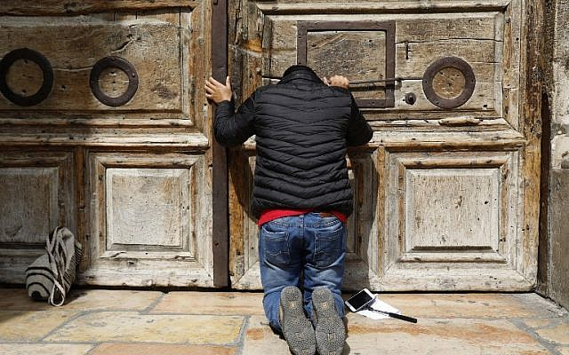 A pilgrim prays outside the closed gate of the Church of the Holy Sepulchre in Jerusalem's Old City on February 25, 2018. (AFP PHOTO / GALI TIBBON)