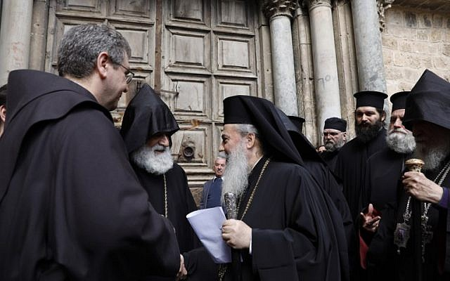 Greek Orthodox Patriarch of Jerusalem Theophilos III delivers a statement to the press as he stands next to the Custodian of the Holy Land Fr. Francesco Patton and Armenian Bishop Siwan, left, on February 25, 2018 as they stand outside the closed doors of the Church of the Holy Sepulchre in Jerusalem's Old City. (AFP/ GALI TIBBON)