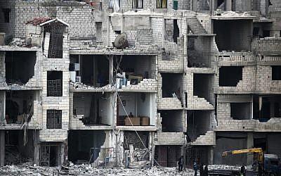 Syrians walk past destroyed buildings in Arbin in the rebel-held enclave of Eastern Ghouta on February 25, 2018. (AFP Photo/Abdulmonam Eassa)