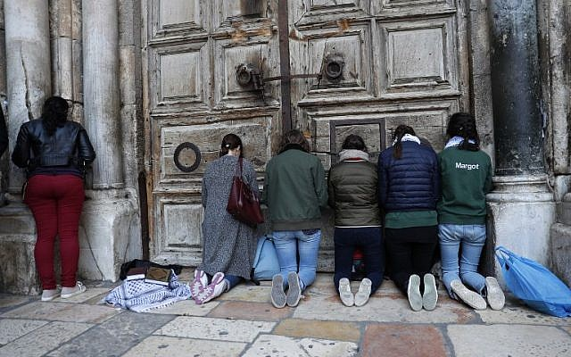 Pilgrims pray outside the closed gate of the Church of the Holy Sepulchre in Jerusalem's Old City on February 27, 2018.(AFP PHOTO / Thomas COEX)