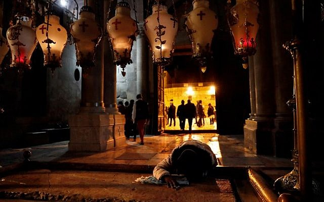 A Christian worshipper prays on the anointing stone inside the Church of the Holy Sepulchre after it reopened on February 28, 2018 following a three-day closure to protest against Israeli tax measures and a proposed law. (AFP/ Thomas COEX)