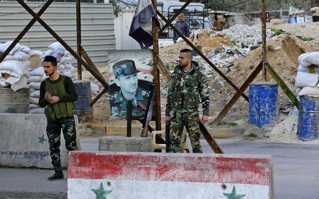 Members of the Syrian government forces stand at the Wafideen checkpoint on the outskirts of Damascus neighboring the rebel-held Eastern Ghouta region on February 28, 2018. (AFP Photo/Louai Beshara)