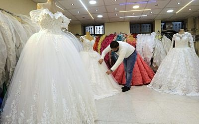 A Syrian man arranges dresses at a wedding gown store in the Syrian capital Damascus on January 8, 2018.  (AFP PHOTO / LOUAI BESHARA)