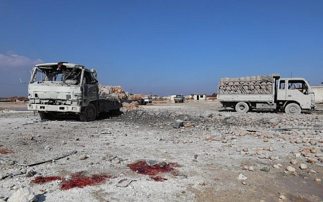 Illustrative: Blood stains on the ground next to trucks loaded with sacks of potatoes standing abandoned, after their windows were blasted from their frames following airstrikes by government forces which hit the vegetable market of the town of Saraqeb in Syria's northwestern province of Idlib, on January 29, 2018. (AFP PHOTO / OMAR HAJ KADOUR)