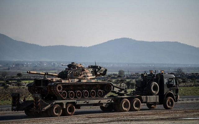 A Turkish military truck carries a tank as it is dispatched to the border in Hatay, near the Turkey-Syria border, on January 31, 2018. (OZAN KOSE/AFP)