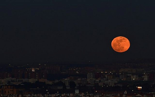 A picture taken on January 31, 2018 shows the moon rising over Madrid. (AFP PHOTO / PIERRE-PHILIPPE MARCOU