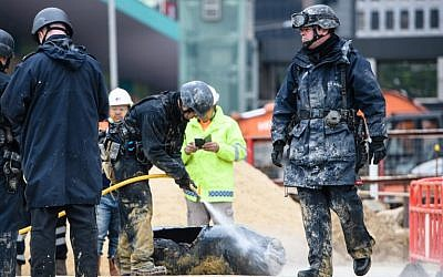 Bomb disposal expert Adam Roberts (R) walks past as a colleague from the explosive ordinance disposal unit hoses down a defused US-made bomb dropped during World War II a day after it was discovered on a harborfront construction site in the Wan Chai district of Hong Kong on February 1, 2018.   (Anthony Wallace/AFP)