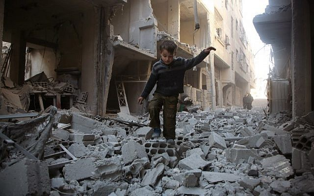 A Syrian boy walks through a street covered with rubble from a heavily damaged building following airstrikes by regime forces in Arbin, in the rebel-held Eastern Ghouta region on the outskirts of the Syrian capital Damascus, on February 1, 2018. (AFP PHOTO / Amer ALMOHIBANY)