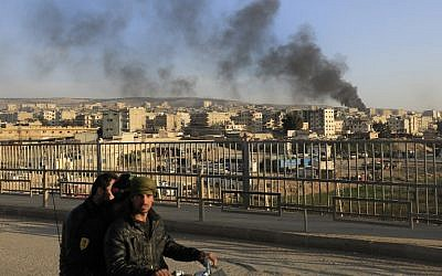 A picture taken in the northern town of Afrin on February 2, 2018, shows smoke from burning tires, used to block the visibility of planes, billowing in the background as people walk on a bridge. (AFP/ Delil souleiman)