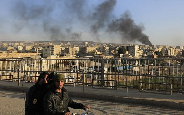 File: A picture taken in the northern town of Afrin on February 2, 2018, shows smoke from burning tires, used to block the visibility of planes, billowing in the background as people walk on a bridge. (AFP/Delil Souleiman)