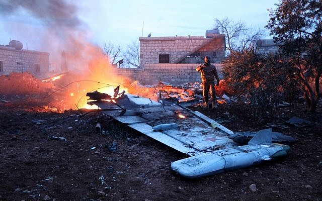 A picture taken on February 3, 2018, shows a Rebel fighter taking a picture of a downed Sukhoi-25 fighter jet in Syria's northwest province of Idlib. (AFP photo)
