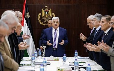 Palestinian Authority President Mahmoud Abbas recites a prayer prior to chairing a meeting of the Palestine Liberation Organization (PLO) Executive Committee at the Palestinian Authority headquarters in the West Bank city of Ramallah on February 3, 2018.  (AFP Photo/Abbas Momani)