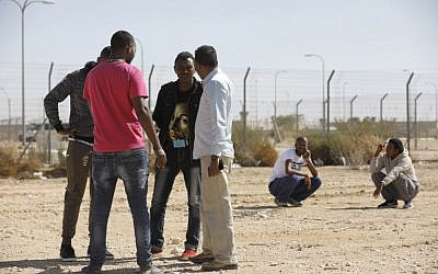 Detained African migrants standing outside the Holot detention center, located in Israel's southern Negev desert near the Egyptian border, February 4, 2018. (MENAHEM KAHANA/AFP)