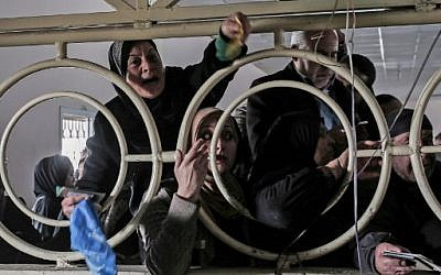 Palestinian women shout as Gazans wait for permission to cross into Egypt through the Rafah border crossing in the southern Gaza Strip after it was opened by Egyptian authorities for humanitarian cases on February 7, 2018. (AFP PHOTO / SAID KHATIB)