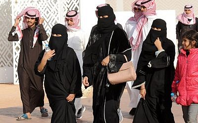 A picture taken on January 19, 2018 shows Saudi women clad in the Abaya robes and men walking during the King Abdulaziz Camel Festival in Rumah, some 160 kilometres east of Riyadh. (AFP PHOTO / FAYEZ NURELDINE)