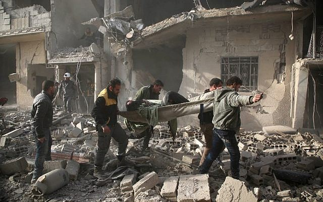 Members of Syrian civil defence forces known as White Helmets evacuate a victim of an air strike in the rebel-held enclave of Arbin in the Eastern Ghouta near Damascus on February 8, 2018. (Amer ALMOHIBANY/AFP)