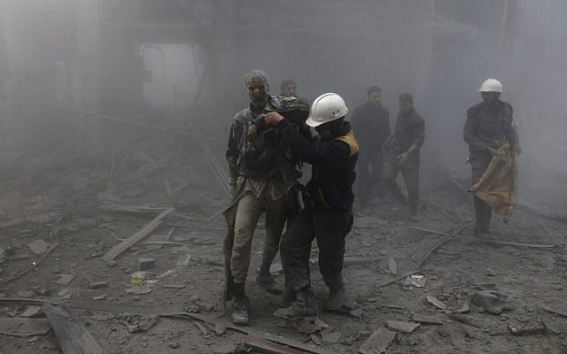 A wounded man is helped out of the destruction following air strikes in the rebel-held enclave of Arbin in the Eastern Ghouta near Damascus on February 8, 2018. (AFP PHOTO / ABDULMONAM EASSA)