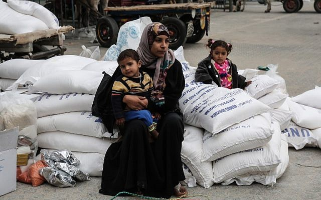A Palestinian woman sits with a child after receiving food supplies from the United Nations' offices at the United Nations' offices in the Khan Yunis refugee camp in the southern Gaza Strip, February 11, 2018. (AFP/Said Khatib)