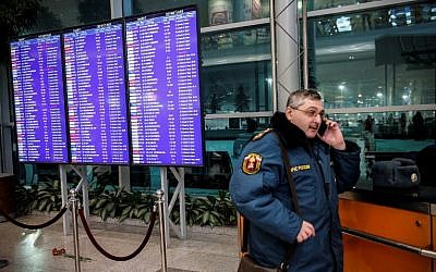 A Russian emergency employee stands next to flowers, in tribute to a plane crash victims, placed under of the flight schedule timetables at the Domodedovo International Airport, outside Moscow, February 11, 2018. (Maxim ZMEYEV/AFP)