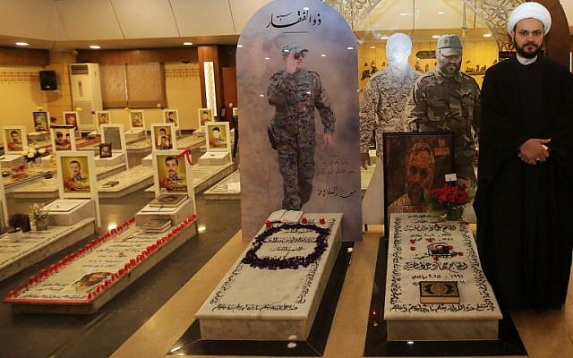 Secretary General of Shitte Iraqi Al-Nujabaa movement Akram al-Kaabi poses for a picture by  the tombs of slain Hezbollah military leaders Imad Moghnieh (R) and Moustapha Badreddine (L) in Beirut's southern suburb on February 13, 2018. (AFP PHOTO / ANWAR AMRO)