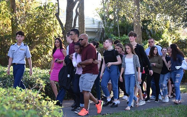 Students react following a shooting at Marjory Stoneman Douglas High School in Parkland, Florida, a city about 50 miles (80 kilometers) north of Miami on February 14, 2018.(AFP PHOTO / Michele Eve Sandberg)