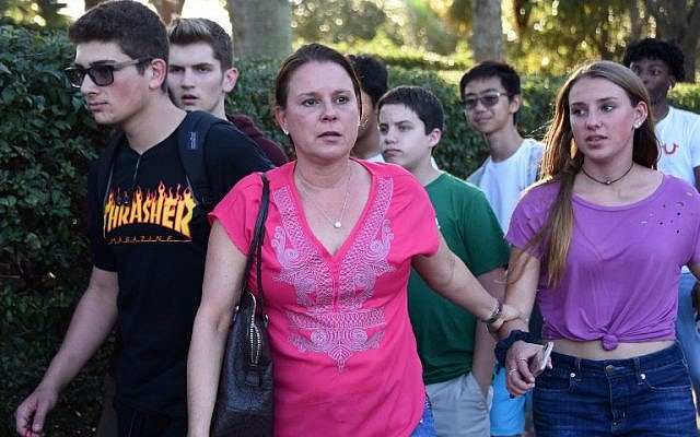 Students and adults leave following a shooting at Marjory Stoneman Douglas High School in Parkland, Florida, a city about 50 miles (80 kilometers) north of Miami on February 14, 2018.(AFP PHOTO / Michele Eve Sandberg)