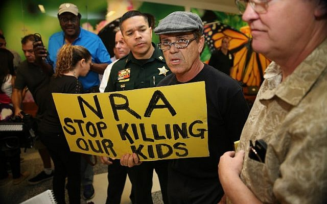 People protest against the National Rifle Association at the Broward County Court House, during the first appearance in court via video link for high school shooter Nikolas Cruz, on February 15, 2018, in Fort Lauderdale, Florida. (AFP Photo/Pool/Charles Trainor/Miami Herald)