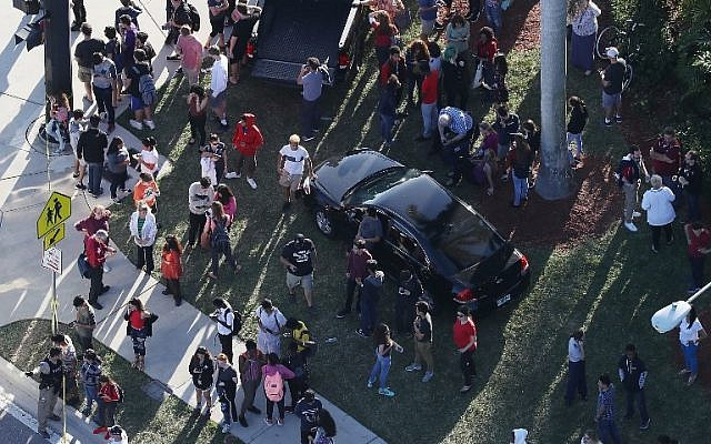 People wait for loved ones as they are brought out of the Marjory Stoneman Douglas High School after a shooting at the school that reportedly killed and injured multiple people on February 14, 2018 in Parkland, Florida. (Joe Raedle/Getty Images/AFP)