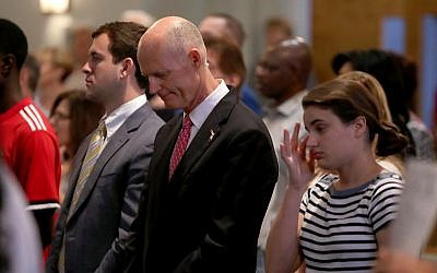 Florida Governor Rick Scott, center, participates in a church service dedicated to the victims of the Marjory Stoneman Douglas High School mass shooting, at the First Church of Coral Springs, on February 18, 2018 in Coral Springs, Florida. Mark Wilson/Getty Images/AFP)